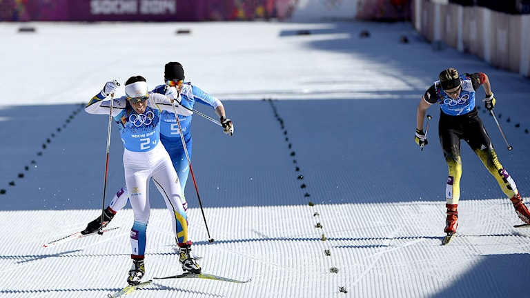 Charlotte Kalla spurtar förbi Finlands  Krista Lahteenmäki ioch Tysklands Denise Herrmann i OS-stafetten i Sotji 2014. Foto: Pierre-Philippe Marcou/TT.