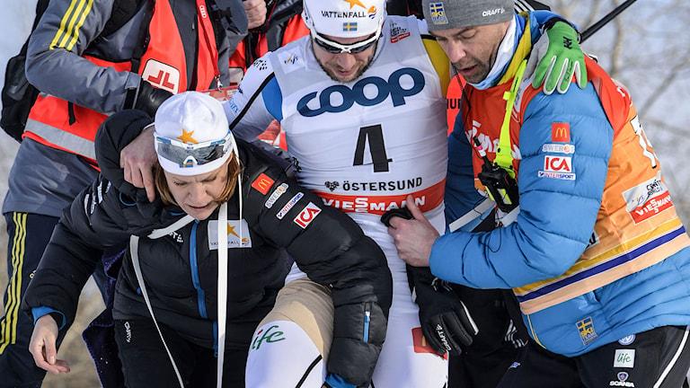 ÖSTERSUND 2015-02-14 Sveriges Emil Jönsson tas omhand av bland annat Rikard Grip (t h) efter skada under sprintkvartsfinalen (k) vid lördagens världscuptävling i Östersund. Foto: Henrik Montgomery / TT.