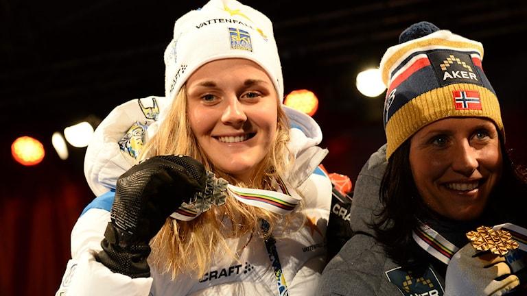 FALUN 2015-02-19 Sveriges Stina Nilsson (tv) och Norges Marit Björgen visar upp sina medaljer under medaljceremonin efter dagens sprinttävlingar på torget i Falun under skid-VM. Foto: Fredrik Sandberg / TT
