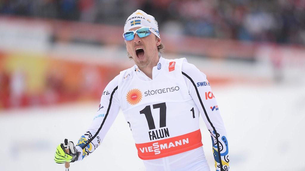 Johan Olsson jublar efter målgången på 15 kilometer. Foto: Fredrik Sandberg/TT