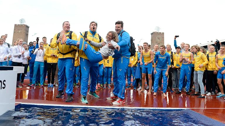 De svenska herrarna firar segern med att kasta förbundskapten Karin Torneklint i vattengraven. Foto: Jessica Gow/TT