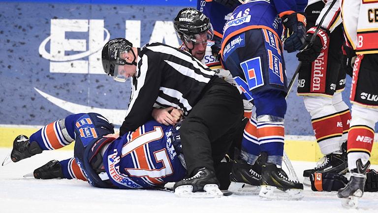 Ishockeyspelare ligger i en hög på isen. Foto: TT Nyhetsbyrån