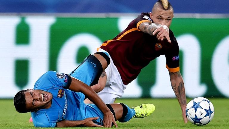 Romas Radja Nainggolan tacklar Barcelonas Rafinha. Foto: ALBERTO PIZZOLI/TT.