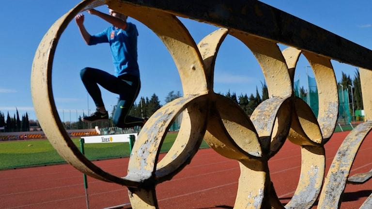 En häcklöpare sedd genom ett räcke med de olympiska ringarna.