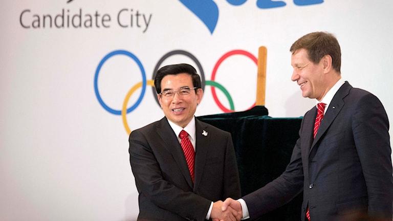 Alexander Zjukov (t.h.) skakar hand med Pekings borgmästare Wang Anshun