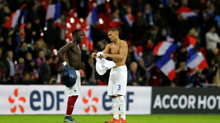 Kieran Gibbs, right, exchanges shirts with France's Bacary Sagna. Foto: TT