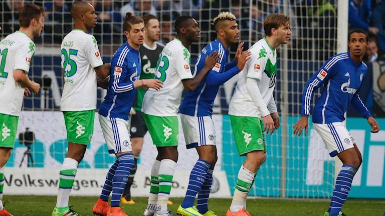 Spelare i Wolfsburg (i vitt) och Schalke (i blått)
