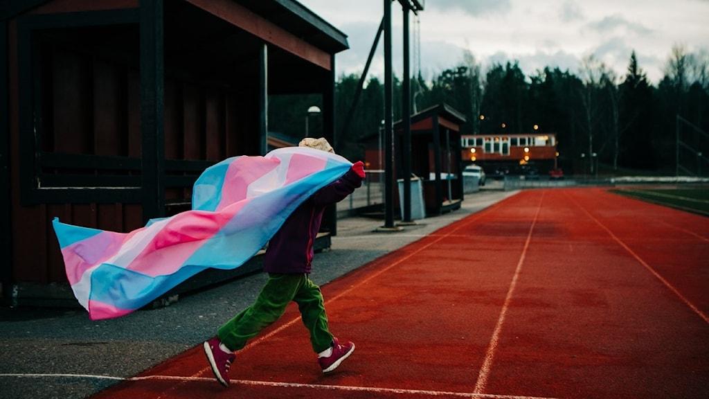 Barn springer med transflaggan