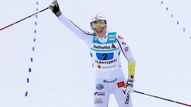 Längdskidåkaren Stina Nilsson jublar när hon passerar mållinjen.
