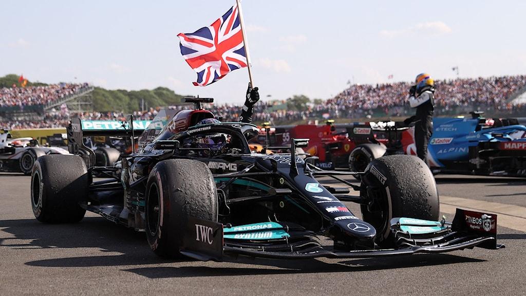 Lewis Hamilton i sin bil med en brittisk flagga i handen.
