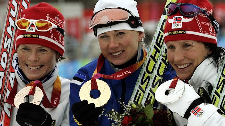 Kristina Smigun i mitten tillsammans med norska duon Hilde Pedersen och Marit Björgen i Turin-OS.