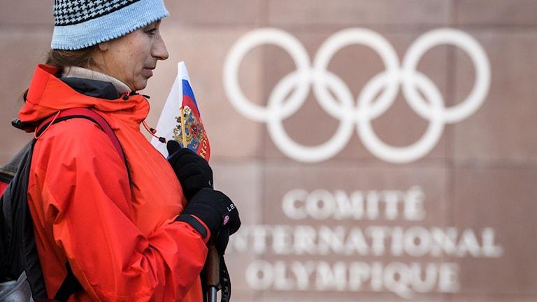 Ryss med flagga framför OS-symbol. Foto: FABRICE COFFRINI/TT