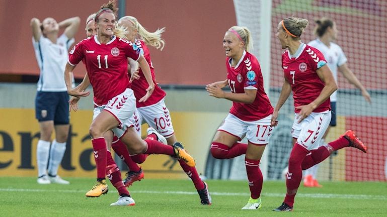 På fotot syns kvinnliga fotbollsspelare från Danmark. De är klädda i röda tröjor och springer över planen.