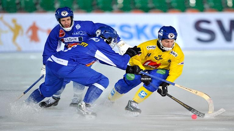 2011-01-23 David Karlsson, Sverige tar sig förbi två finska spelare, i matchen som slutade 9-8 till Finland under söndagens bandy VM match mellan Sverige och Finland på Trudovye Rezervy stadion i Kazan i Ryssland.Foto: Niklas Larsson / SCANPIX