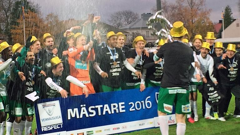 IFK Mariehamn, med lagkaptenen Jani Lyyski med ryggen mot kameran, firar guldet.