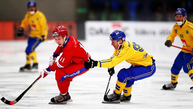 Rysslands Vadim Chernov mot Sveriges Erik Pettersson under lördagens match i grupp A mellan Sverige och Ryssland i bandy-VM på Arena Vänersborg.