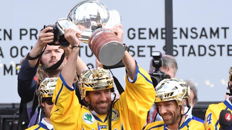 Henrik Lundqvist lyfter bucklan och hans bror Joel står bredvid under guldfirandet på Sergels Torg.