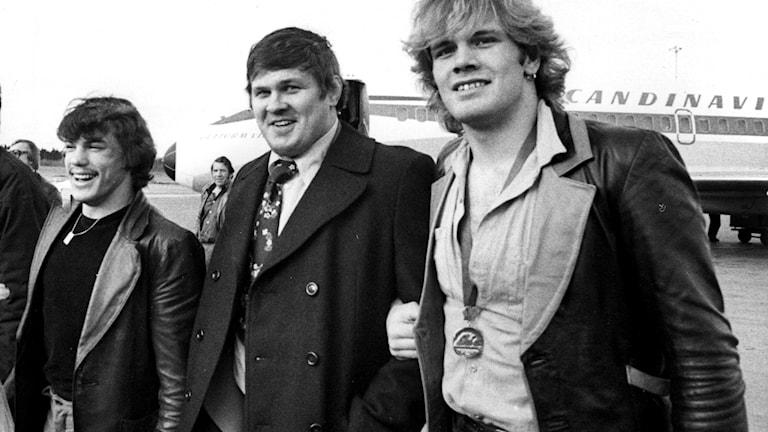ARKIV STOCKHOLM 1976-04-25  De svenska guldmedaljörerna vid Europamästerskapen i brottning i Leningrad, Sovjetunionen, Lars-Erik Skiöld (t. v.) och Frank Andersson (t. h.) anländer till Arlanda flygplats 25:e april 1976 i sällskap med brottarbasen Pelle Svensson mellan sig. Lars-Erik vann i 68 kilosklassen och Frank i 90 kilosklassen båda i grekisk-romersk stil.  Foto: Gunnar Lantz / SvD / TT