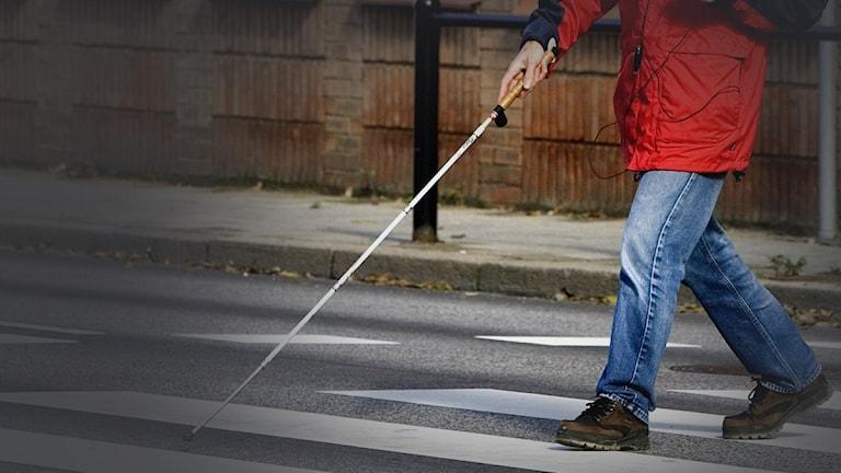 En synskadad man går över ett övergångställe med hjälp av en blindkäpp.