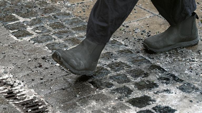 Person iklädd stövlar går på hal asfalt.