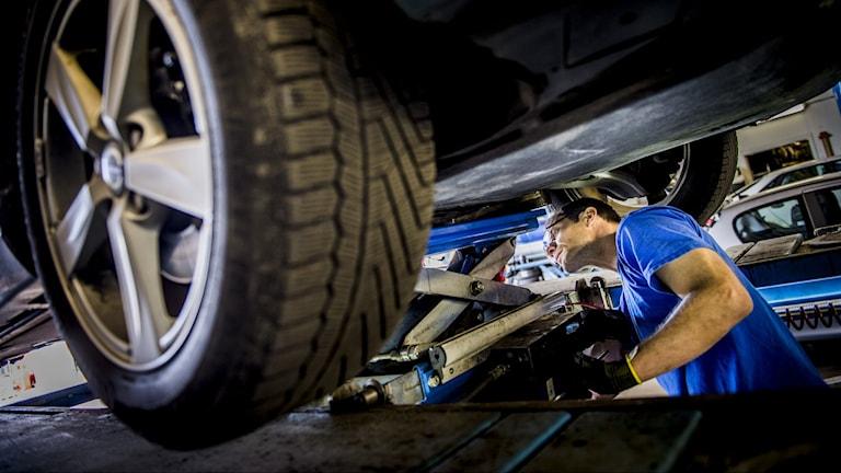 En bilmekaniker arbetar med en bil.