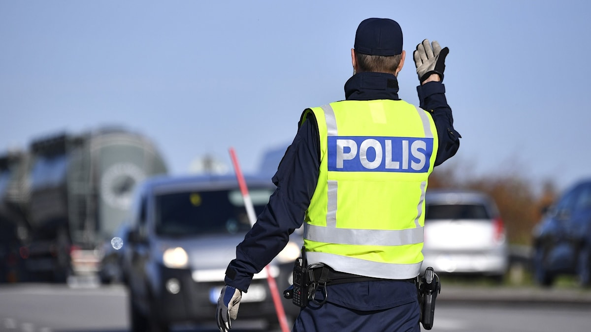Polisman vinkar in bilist.