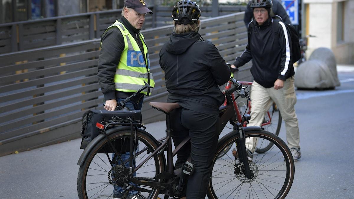 En polis pratar med en cyklist.