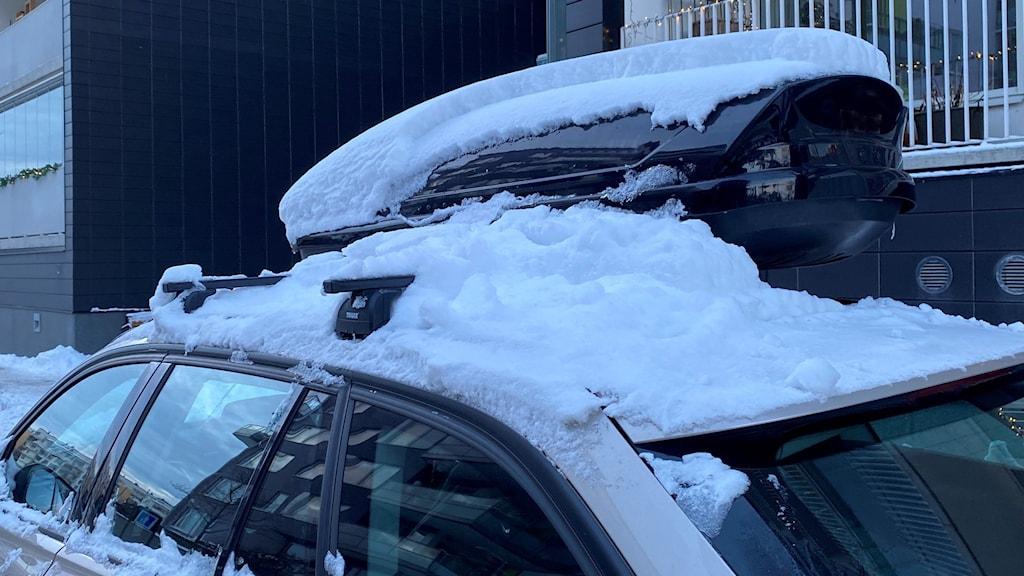 Mycket snö som ligger på en bil med takbox.