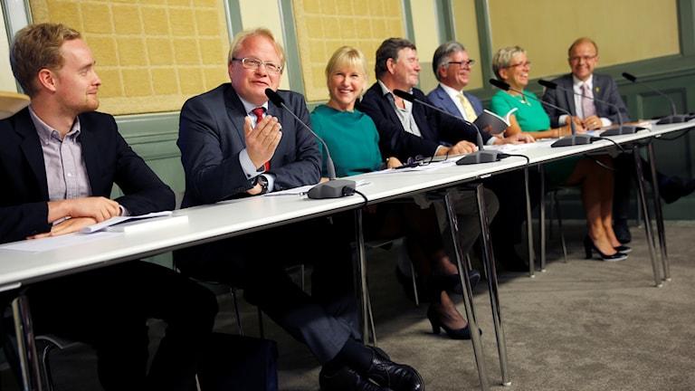 Ministerit istuvat vierekkäin pöydän ääressä lehdistötilaisuudessa.