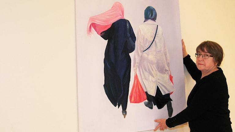 Liisa Harju ripustamassa yhtä siirtolaisuutta käsittelevää tauluaan Boråsin suomiseuran huoneistossa.