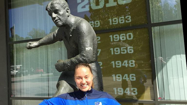 Iloinen Tanya Näsman Gunnar Nordahlin -patsaan edessä.