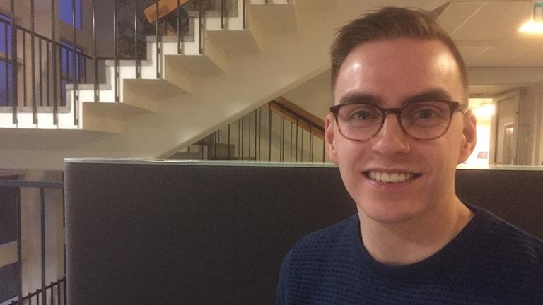 Silmälasipäinen Matti Myllyaho katsoo hymyillen kameraan, taka-alalla portaikko. Kuva: Timo Laine/SR Sisuradio