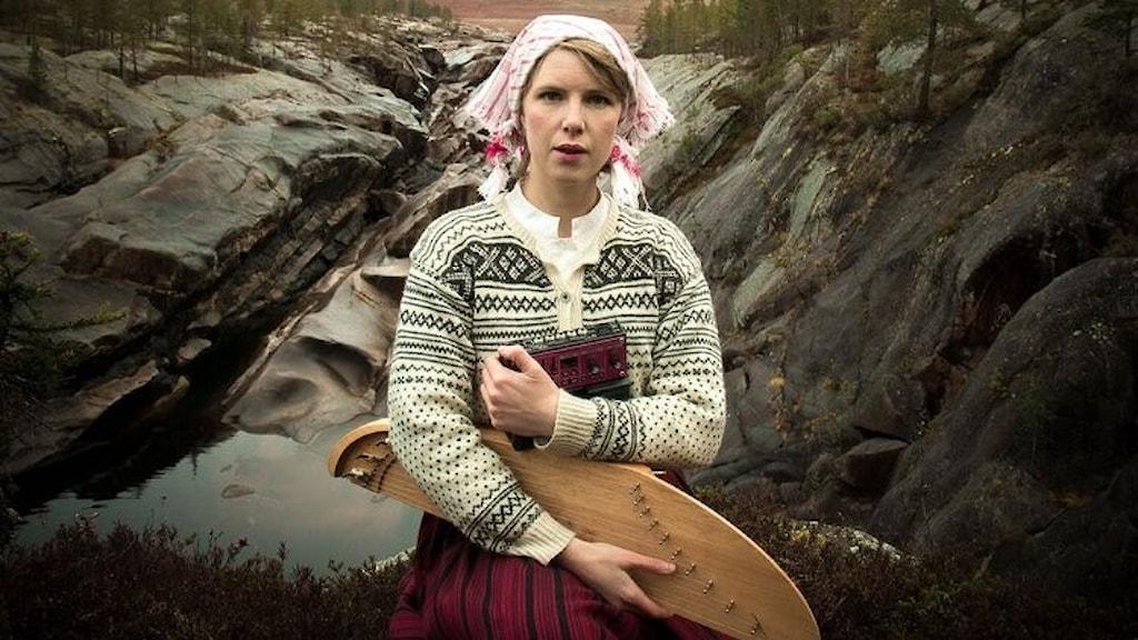 Konstnären Mirja Palo utomhus i kargt och stenigt Norrbottenlandskap med en kantele i famnen.
