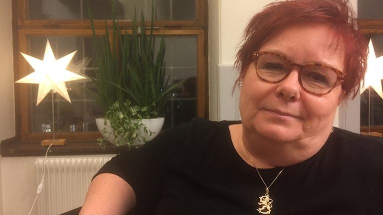 Punahiuksinen Mirja Räihä istuu toimistossa katsoen kameraan kaulassaan Suomen leijona-koru, taustalla huonekasvi ja jouluntähtivalaisin. Kuva: Timo Laine/SR Siradio
