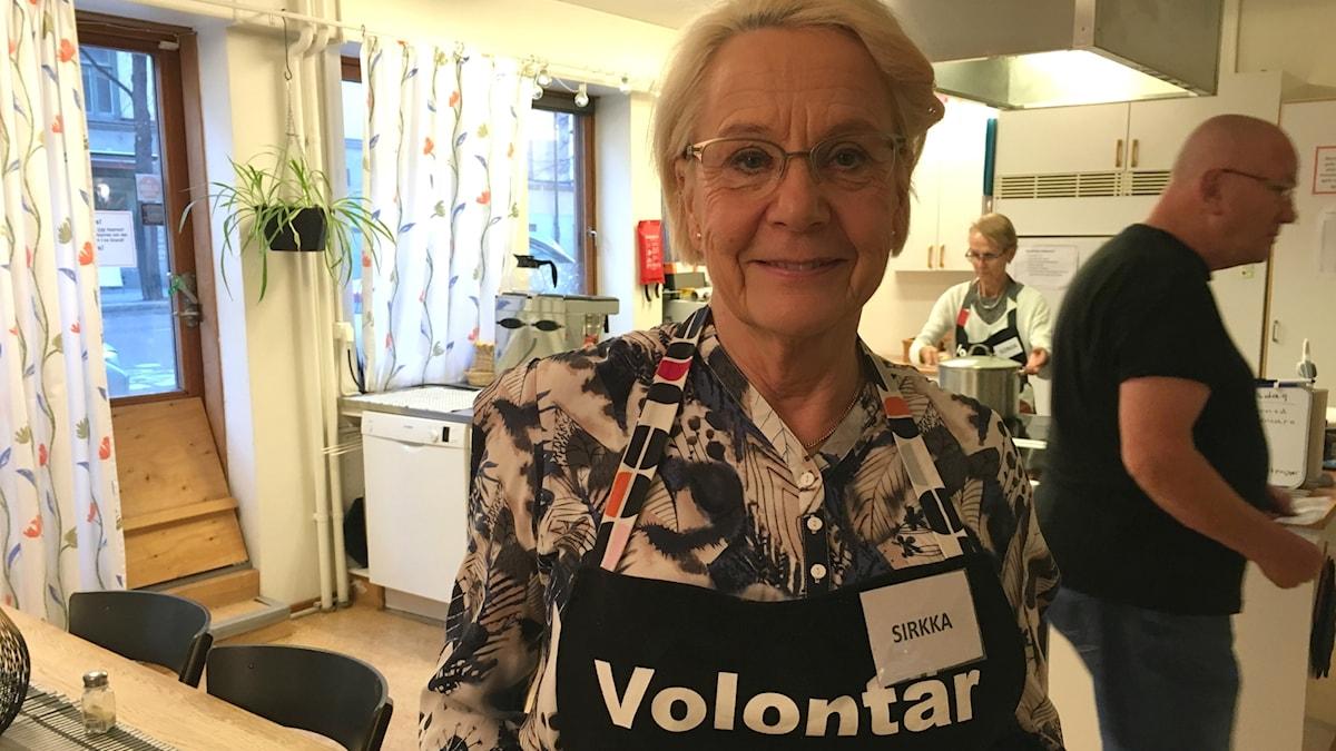 Sirkka Gustafsson seisoo keittiössä volontäär-esiliinassa Stockholms stadsmissionin keittiössä.