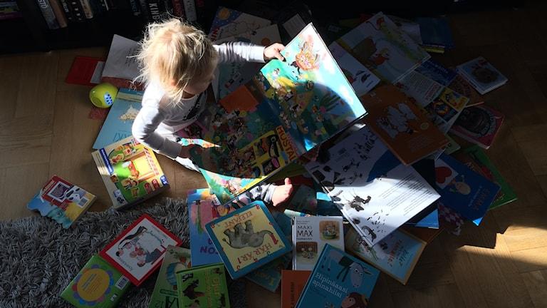 Ett barn sitter på golvet och läser böcker.