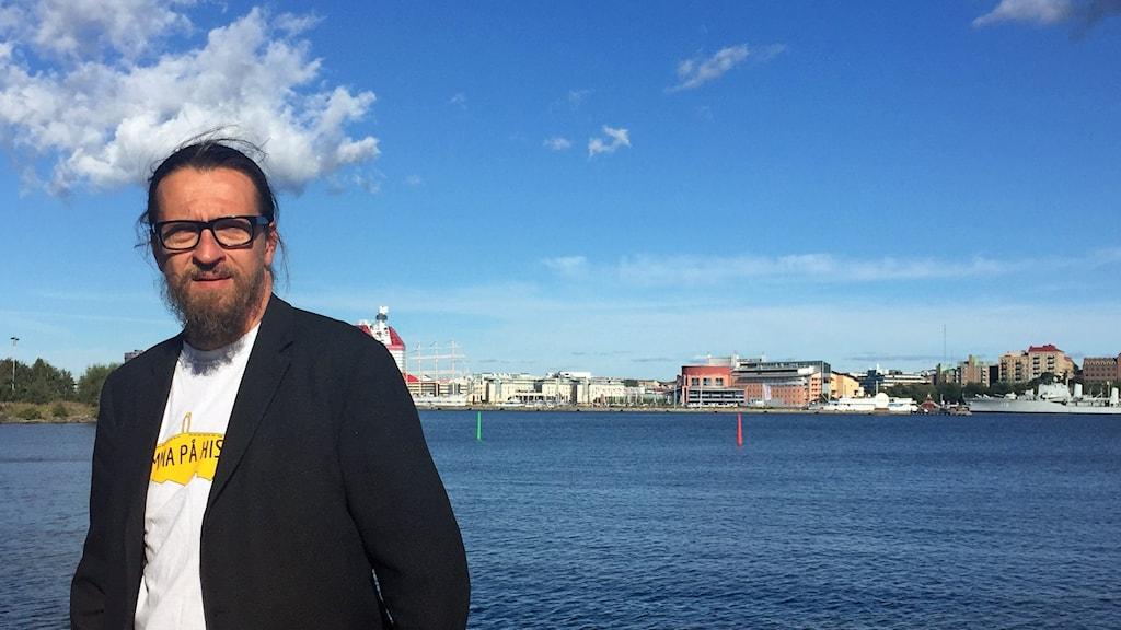 En man med en svart kavaj och glasögon, vatten och Göteborgs sluett i bakgrunden