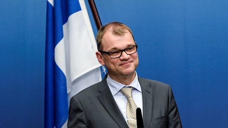 Juha Sipilä ja Suomen lippu.
