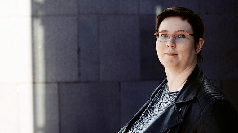 Merja Kyllönen står mot en mörk vägg