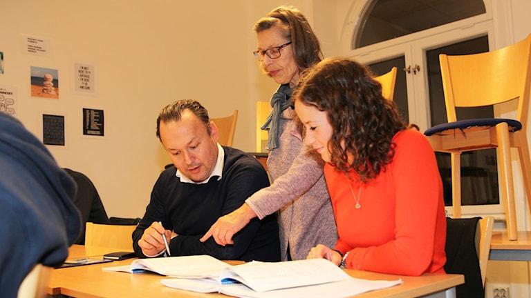 Suomen kielen opettaja Anna-Maija Itkonen opastaa alkeiskurssilaisia Hasan Karatasta ja Ida Hinkkasta.