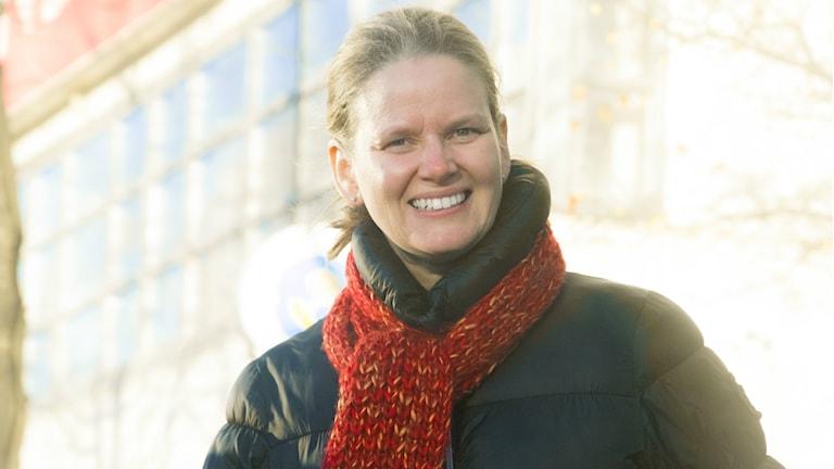 Kuvassa mustaan toppatakkiin ja punaiseen kaulahuiviin pukautunut Heidi Raita.