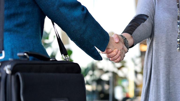 Kaksi henkilöä kättelevät