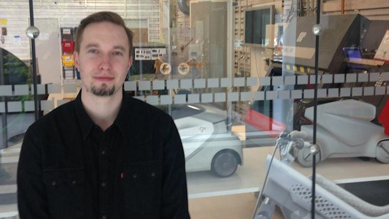 Mustapaitainen Sami Laiho seisoo muotoilulaboratorion lasiseinän edessä taustanaan erilaisia muotoilukonsepteja.