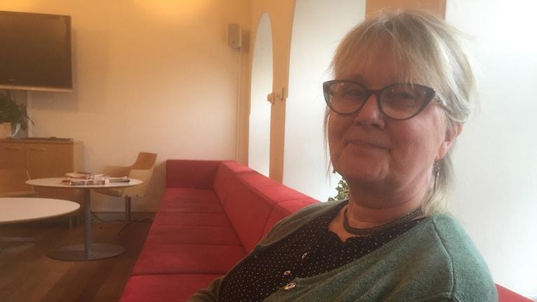 Silmälasipäivnen Mirjaliisa Lukkarinen Kvist istuu pitkällä punaisella sohvalla vihreä neule päällään. Kuva: Timo Laine/SR Sisuradio