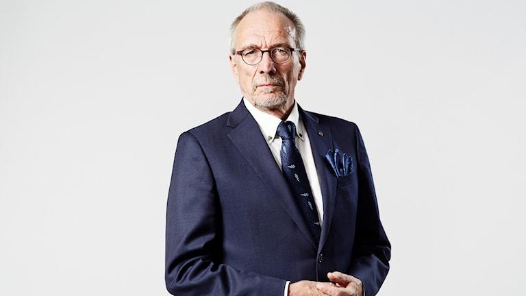 RKP:n Nils Torvalds lehdistökuvassaan, puku päällä, vakava ilme