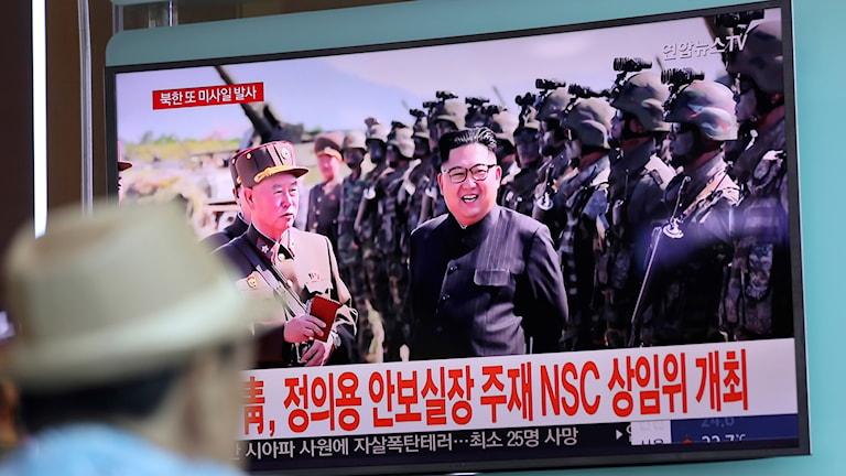 En man tittar på en tv där Kim Yong Un står med en grupp soldater