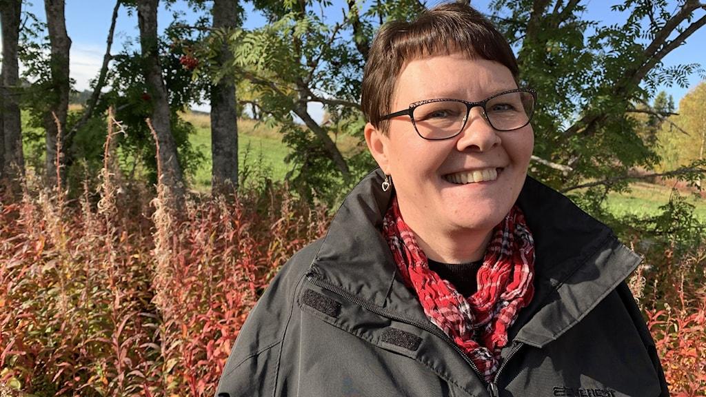 Keski-ikäinen, silmälasipäinen ja lyhyttukkainen, ruskeahiuksinen nainen hymyilee lähikuvassa ulkona päällystakissa ja punaisessa huivissa ruskamaisema taustallaan.