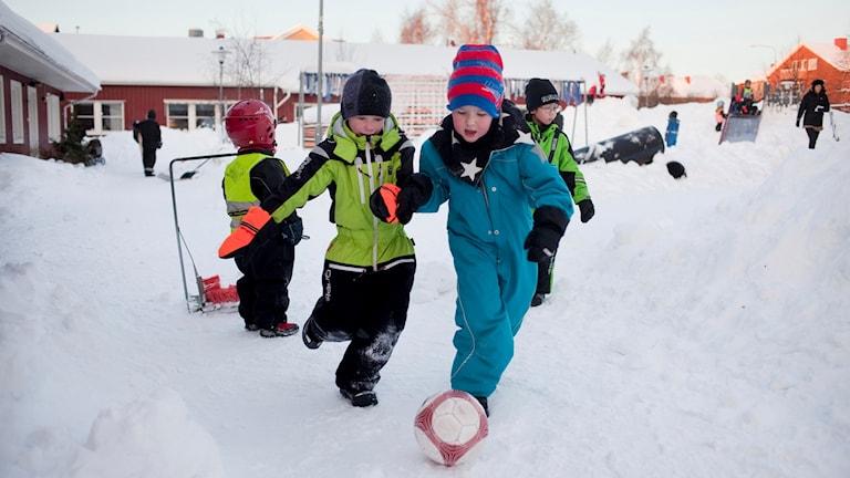 Lapset pelaavat jalkapalloa lumessa