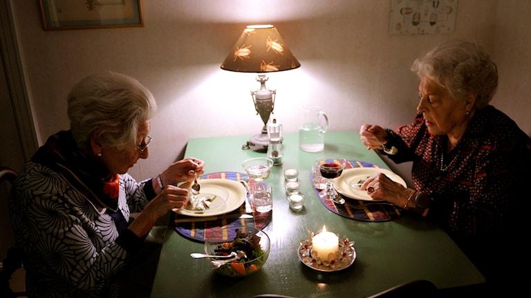 Kaksi vanhaa ystävätärtä seurustelevat ruokapöydässä.