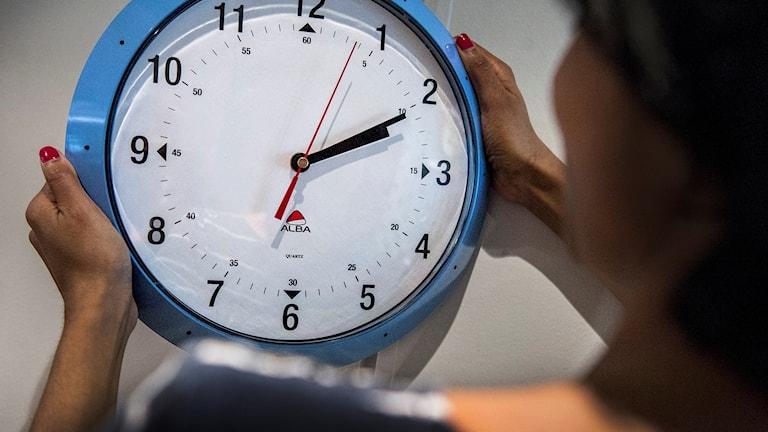 En kvinna hänger upp en klocka.